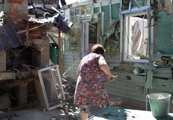 Žena uklízí vedle domu v Doněcku po ostřelování. - Sputnik Česká republika