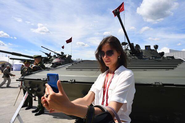 Návštěvnice u bojového vozidla pěchoty BVP-2 na Mezinárodním vojensko-technickém fóru Army 2019. - Sputnik Česká republika