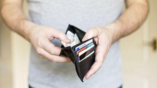 Muž drží peněženku s penězi - Sputnik Česká republika