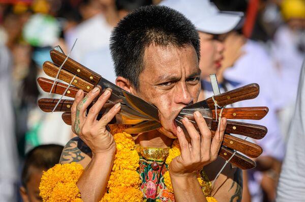 Účastník festivalu vegetariánství s propíchnutými noži ve tvářích v Thajsku. - Sputnik Česká republika