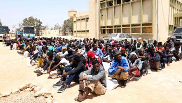 Migranti z Afriky sedí v blízkosti centra pro nelegální migranty v Misuratu - Sputnik Česká republika