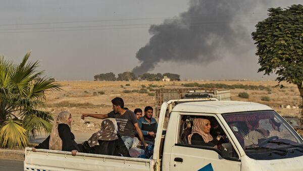 Lidé utíkají před tureckým náletem na město Ras al-Ain v syrské provincii Hasaka (9. 10. 2019) - Sputnik Česká republika