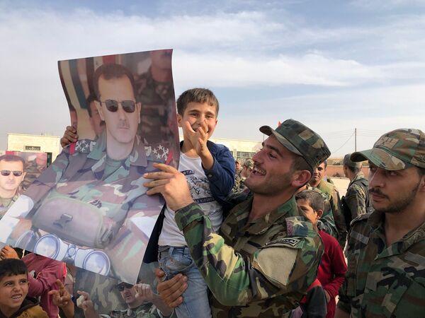Děti a vojáci s plakáty se syrským prezidentem Bašárem Asadem ve městě Manbidž, které bylo osvobozeno syrskou vládní armádou. - Sputnik Česká republika