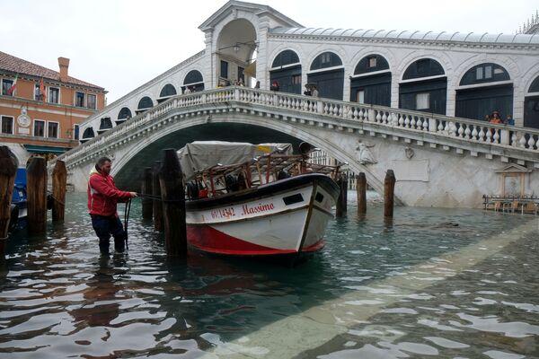 Muž připoutává loď k mostu během povodně v Benátkách - Sputnik Česká republika