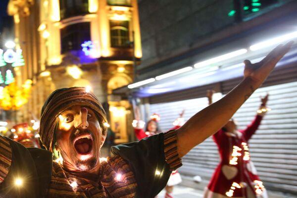 Muž v masce Pinocchia na vánočním karnevalu v brazilském São Paulu - Sputnik Česká republika