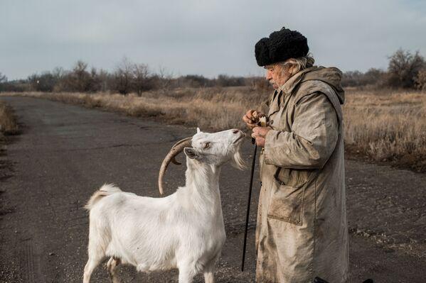 Starší muž s kozou ve vesnici Doněcké v Luhanské oblasti na Ukrajině - Sputnik Česká republika