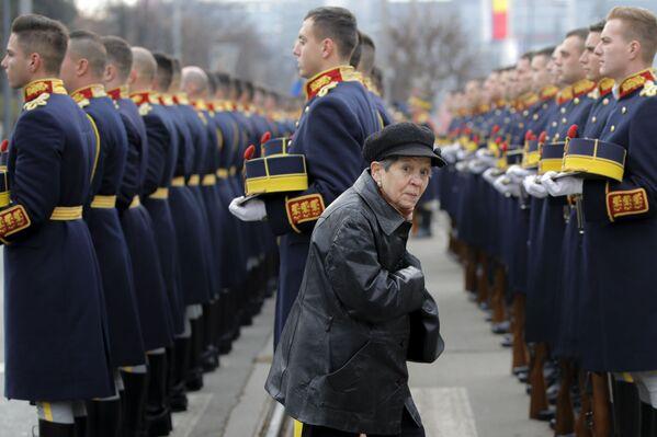 Žena míjí čestnou stráž na Hřbitově hrdinů během 30. výročí protikomunistického povstání v Rumunsku - Sputnik Česká republika