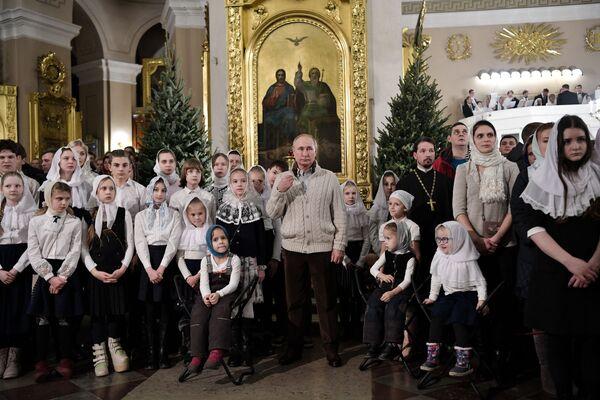 Ruský prezident Vladimir Putin během vánoční bohoslužby v Petrohradě - Sputnik Česká republika