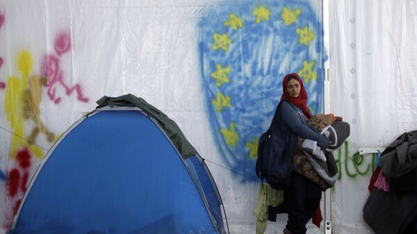 Беженка на фоне нарисованного флага ЕС в палаточном лагере для мигрантов и беженцев в Греции - Sputnik Česká republika