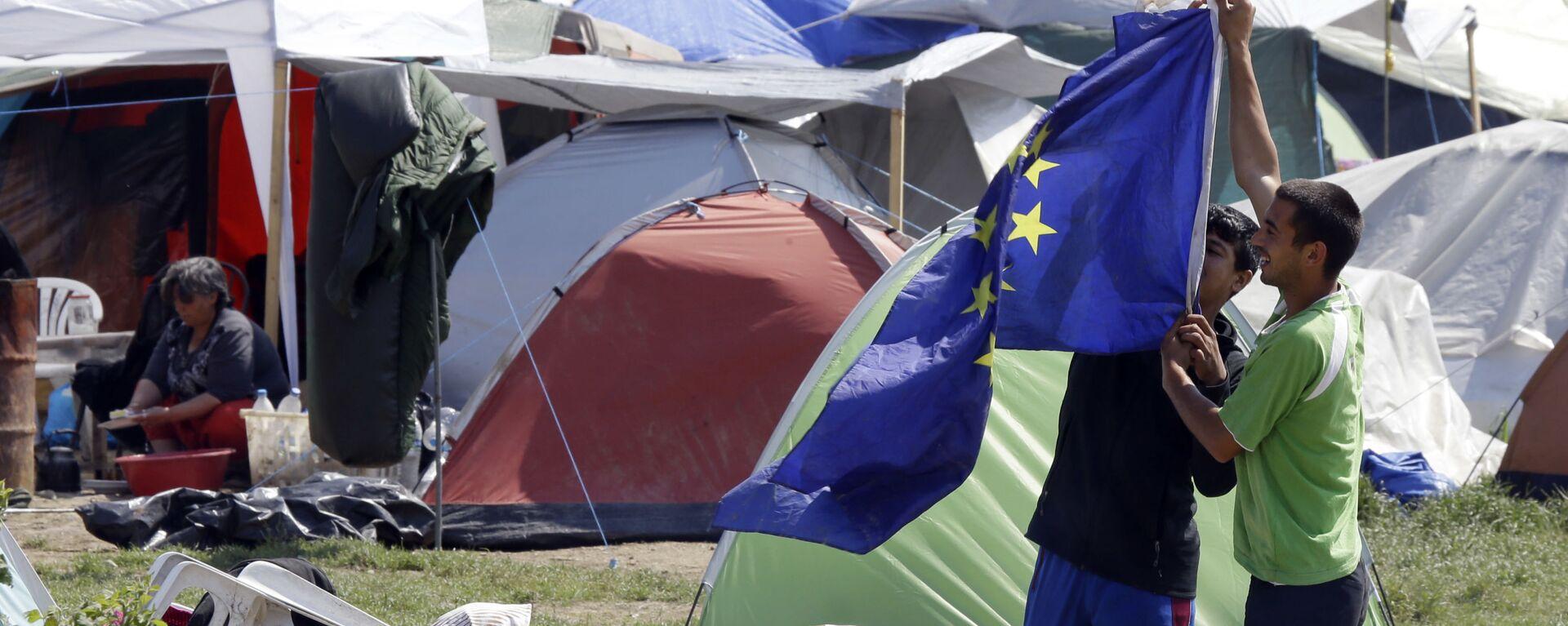Мигранты с флагом ЕС в палаточном лагере для мигрантов и беженцев в Греции - Sputnik Česká republika, 1920, 17.07.2021