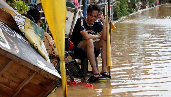 Muž sedí u zatopeného domu v Jakartě - Sputnik Česká republika