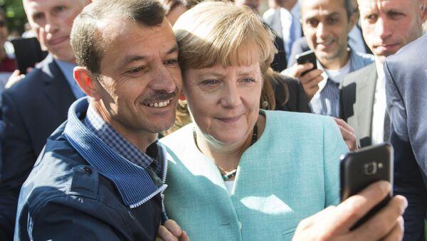 Uprchlík se fotí s německou kancléřekou Angelou Merkelovou - Sputnik Česká republika