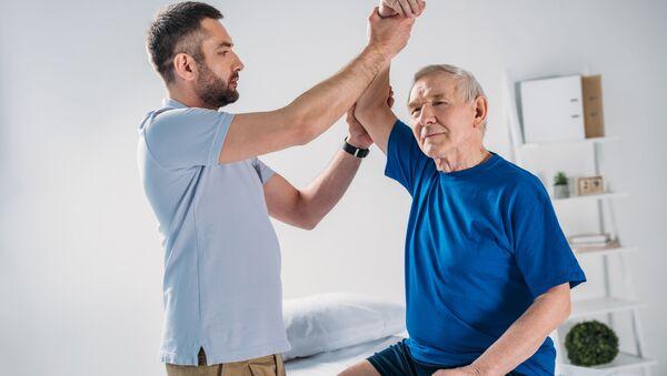 Terapeut dělá masáž staršímu pacientovi - Sputnik Česká republika