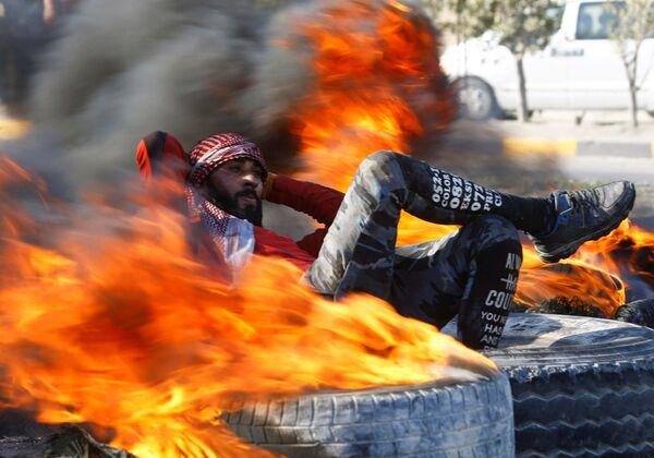 Demonstrant v Iráku sedí mezi hořícími pneumatikami, které blokují cestu během protivládních protestů v Nadžafu - Sputnik Česká republika