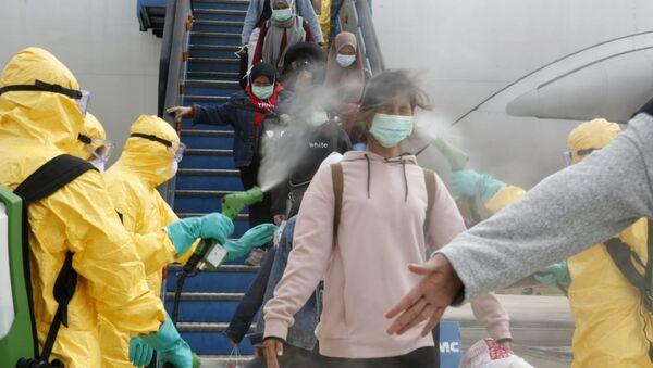Медики опрыскивают индонезийских граждан антисептиком после прибытия из китайского Уханя, центра эпидемии коронавируса - Sputnik Česká republika