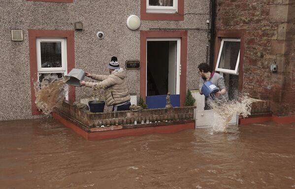 Muži nabírají vodu ze zatopeného domu. Appleby-in-Westmorland, Velká Británie. - Sputnik Česká republika