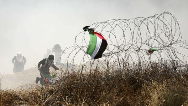 Palestinský protestujicí během střetu s izraelskými vojáky na hranici mezi Pásmem Gaza a Izraelem - Sputnik Česká republika