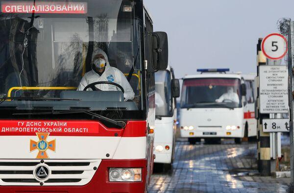 Autobus vyzvedává občany Ukrajiny a dalších zemí, kteří byli evakuováni z Wu-Chanu, na letišti v Charkově. - Sputnik Česká republika