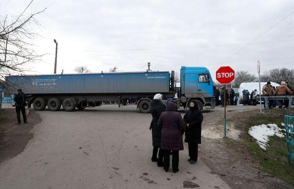 Kamion s návěsem blokuje silnici během protestní akce proti rozmístění evakuovaných občanů z Wu-Chanu v Poltavské oblasti. - Sputnik Česká republika