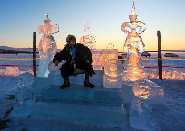 Muž sedí na ledovém trůnu, který byl představen na Mezinárodní soutěži ledových soch v rámci festivalu Olkhon Ice Fest u jezera Bajkal v Irkutské oblasti, Rusko - Sputnik Česká republika