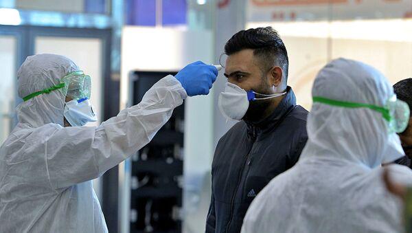 Zdravotnický personál na iráckém letišti Nadžaf kontroluje cestující, kteří přiletěli z Íránu - Sputnik Česká republika