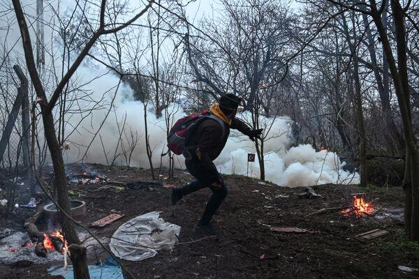 Mladík hází kámen na řecké policisty na turecko-řeckém hraničním přechodu Pazarkule. - Sputnik Česká republika
