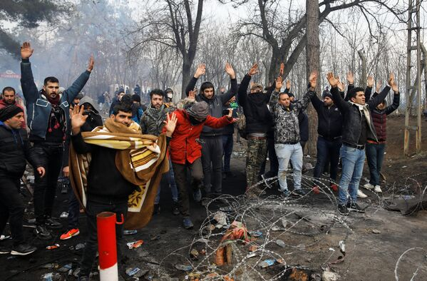 Migranti zvedají ruce na tureckém hraničním přechodu do Řecka Pazarkule. - Sputnik Česká republika