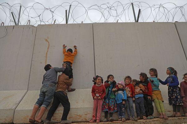 Syrské děti se snaží dostat se přes tureckou hraniční zeď na severozápadě Sýrie - Sputnik Česká republika