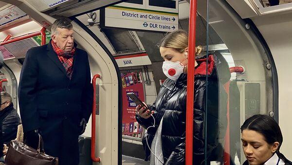 Žena v roušce v londýnském metru - Sputnik Česká republika