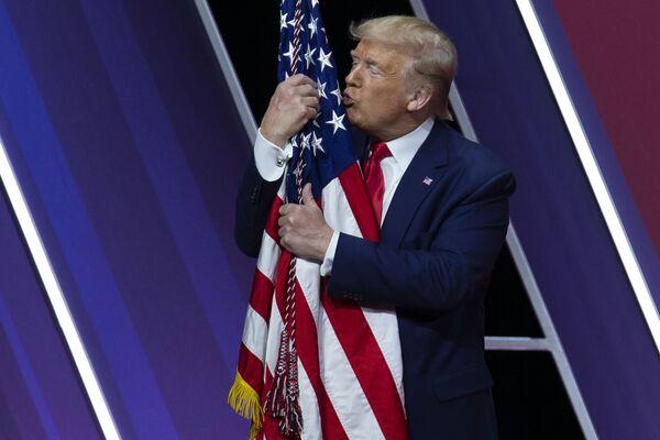Donald Trump líbá americkou vlajku - Sputnik Česká republika