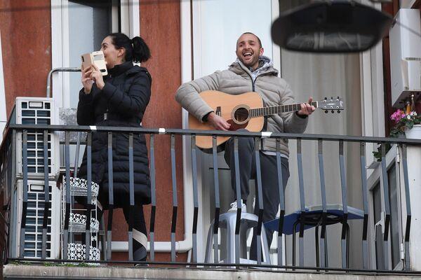 Muž s kytarou a žena s telefonem na balkóně v Miláně - Sputnik Česká republika