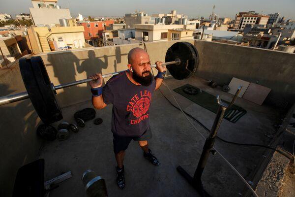 Osama Hussein cvičí na střeše svého domu ve městě Irbíl, Irák - Sputnik Česká republika