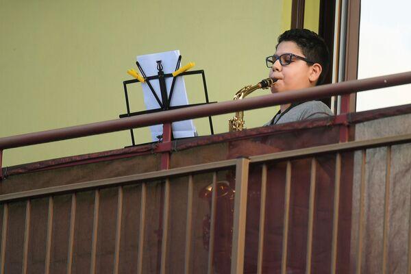 Chlapec hraje na saxofon na balkóně ve městě Milán, Itálie - Sputnik Česká republika