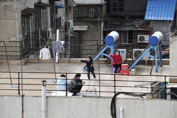 Lidé sedí na střeše domu. Wu-chan, Čína - Sputnik Česká republika