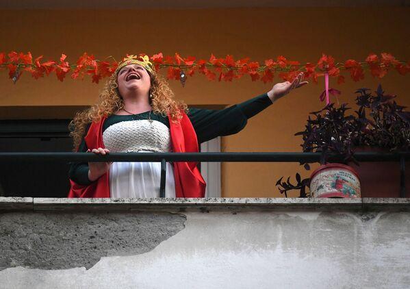 Žena zpívá na svém balkóně během karantény v Římě - Sputnik Česká republika