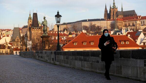 Žena v roušce stojící na prázdném Karlově mostě - Sputnik Česká republika