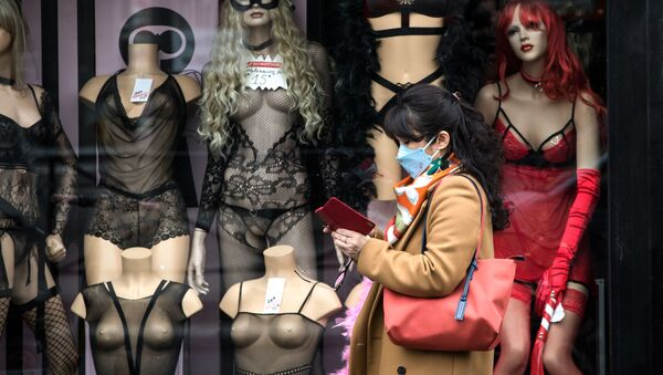 Žena v roušce se prochází kolem výloh uzavřeného obchodu s erotickým zbožím v Paříži, 16. března 2020 - Sputnik Česká republika