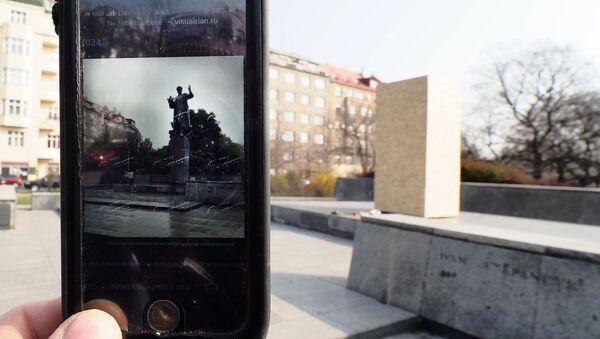 Fotografie pomníku maršálovi SSSR Ivanu Konevoví v Praze na obrazovce telefonu na pozadí náměstí Interbrigády, kde byl demontován - Sputnik Česká republika