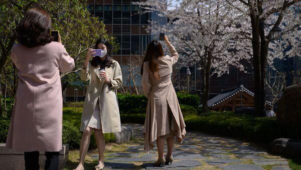 Pracovníci kanceláří v ochranných maskách v centru Soulu - Sputnik Česká republika