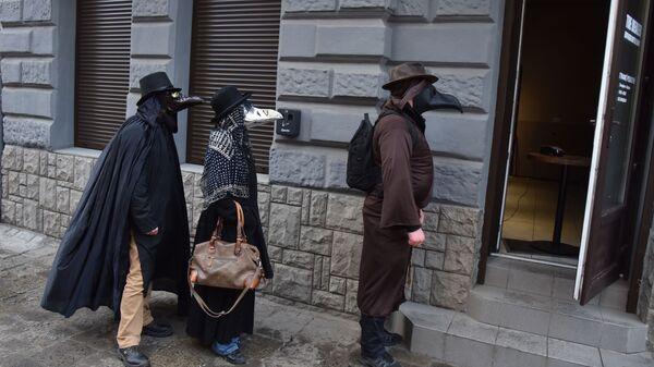 Lidé v kostýmech morových lékařů na ulici Lvova, Ukrajina - Sputnik Česká republika