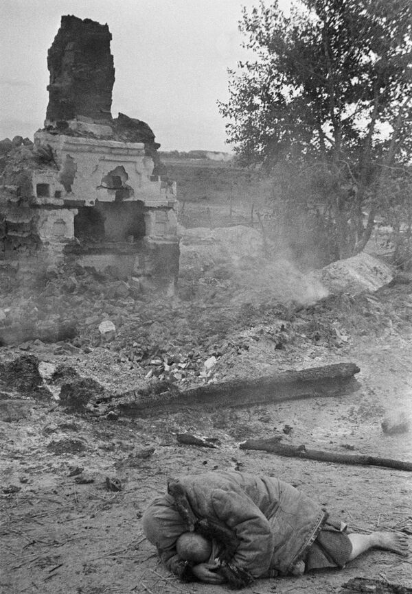 Matka ukrývá své dítě během ostřelování. Vesnice Krasnaja Sloboda, Brjanská fronta, 1941. - Sputnik Česká republika