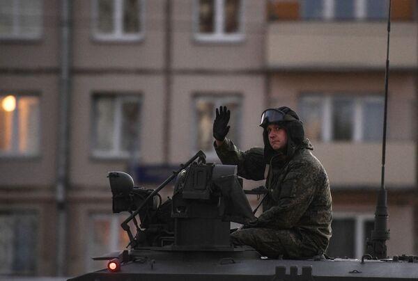Voják - tankista reaguje přátelským pozdravem na fotografa. - Sputnik Česká republika