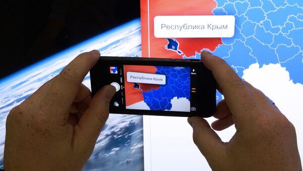 Muž fotografuje mapu Ruska - Sputnik Česká republika