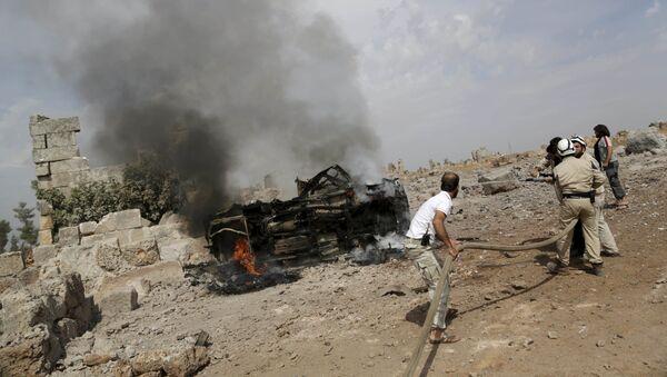 Členové civilní obrany uhasili plameny na hořícím vojenském vozidle v jižním Idlibu, Sýrie 1. října 2015 - Sputnik Česká republika