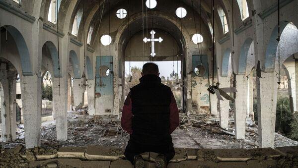 Syřan se modlí v chrámu, který byl zničen Daiš - Sputnik Česká republika