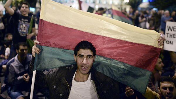 Muž drží vlajku syrské kurdské Strany demokratické unie (PYD) - Sputnik Česká republika