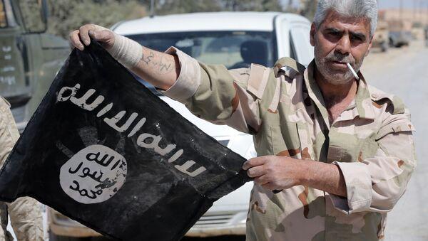 Syrský voják s vlajkou Daiš - Sputnik Česká republika