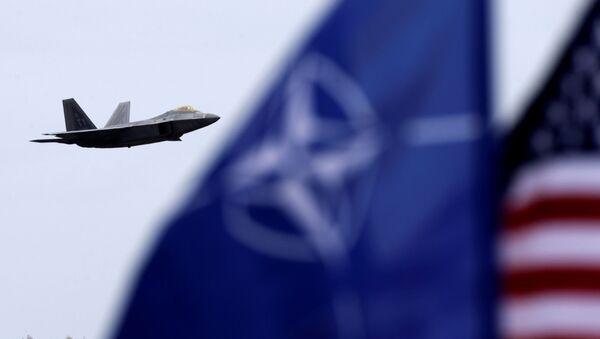 F-22 Raptor na pozadí vlajek USA a NATO - Sputnik Česká republika