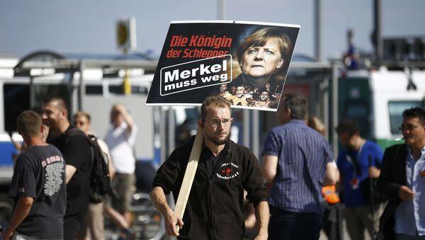 Muž s plakátem Merkelová musí odejít - Sputnik Česká republika