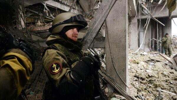 Self-defense fighter known by his nickname of Motorola stands inside a destroyed airport building in the eastern Ukrainian city of Donetsk, on February 26, 2015 - Sputnik Česká republika